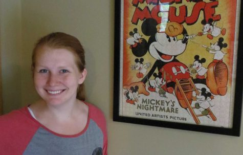 Senior Laura Serier posed by one of the many posters in her Disney themed basement.