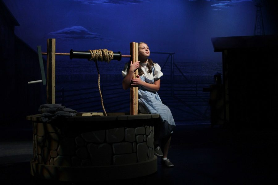 Junior Jayna Davis perched upon  a well during rehearsals for the upcoming play.