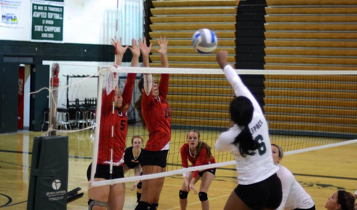 Evans and teammate go up to block an opposing spike during a late season game against Roseville. Evans great leadership showed after stuffing this spike