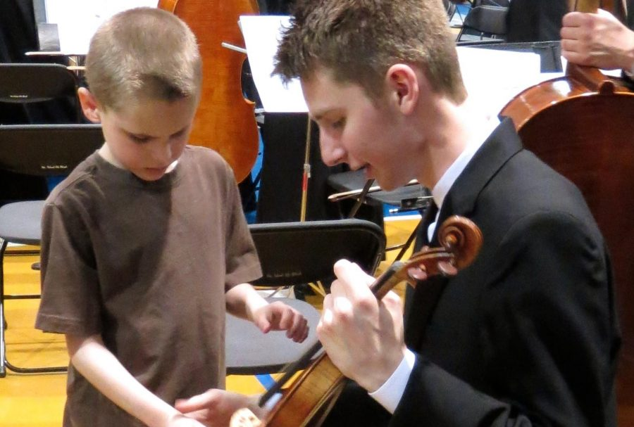 Senior Nick Alm lets a Kansas State School for the Blind student touch a violin after a performance while on tour to Kansas City on April 10-13.