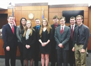 "Pictured are senior Nick Sabin, senior Rachel Hartwig, senior Holly Fena, junior Justin Hannasch, junior Natalie Sims, senior Alex Eitzman, senior Alexander Screaton, senior Mitchell Sell, and senior Adam Johnson. The relationships formed through Mock Trial will last much longer than the time they spend together in the courtroom. Junior Natalie Sims said, ""I'm so sad to say goodbye to the seniors. They were so helpful with everything. You become so close to these people and they are almost like a family and it's weird not seeing them everyday now. I could always count on them if I had any problems with Mock Trial or just personally. It's going to be hard to say goodbye to all of them."""