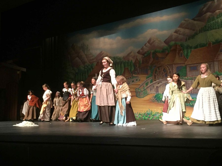 """Mary Burchill ('17) stand as Cinderella on stage during a rehearsal for the upcoming musical Cinderella. """"I think my favorite part is the community that we form,"""" said Junior Emily Heidick. """"There is just something about doing a show together that creates a family."""""""