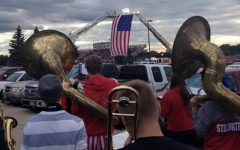 The American Flag in the background hangs in remembrance of those lost on 9/11. The pep band dedicated their performance to those lost 12 years ago. </strong><br /> Photo By Lily Marchan
