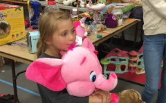 A young girl clutches her new favorite stuffed animal.