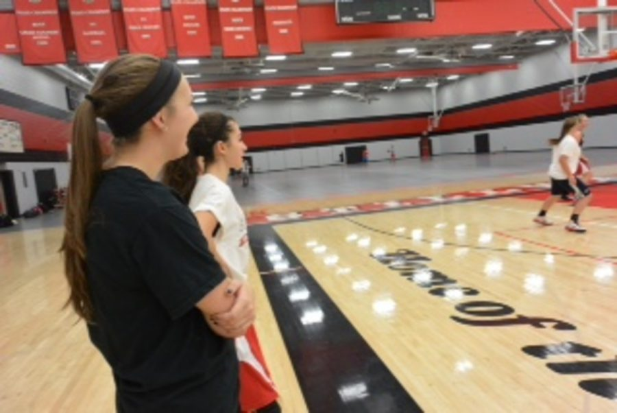 """While their teammates are scrimmaging on the court in front of them, juniors Kaeli Murphy and Natalie Zinn are watching them play. As the girls have a chance to watch their friends and peers play in front of them they can't help but become excited about the game. The players have a lot to smile about on and off the court, but this is not only because of their fellow players. The girls under coach Taylor have had a significantly more enjoyable season, and like playing for him in general. Player parent Eric Davis explains that """"the girls enjoy playing for Coach Taylor and they respect his knowledge of the game"""""""