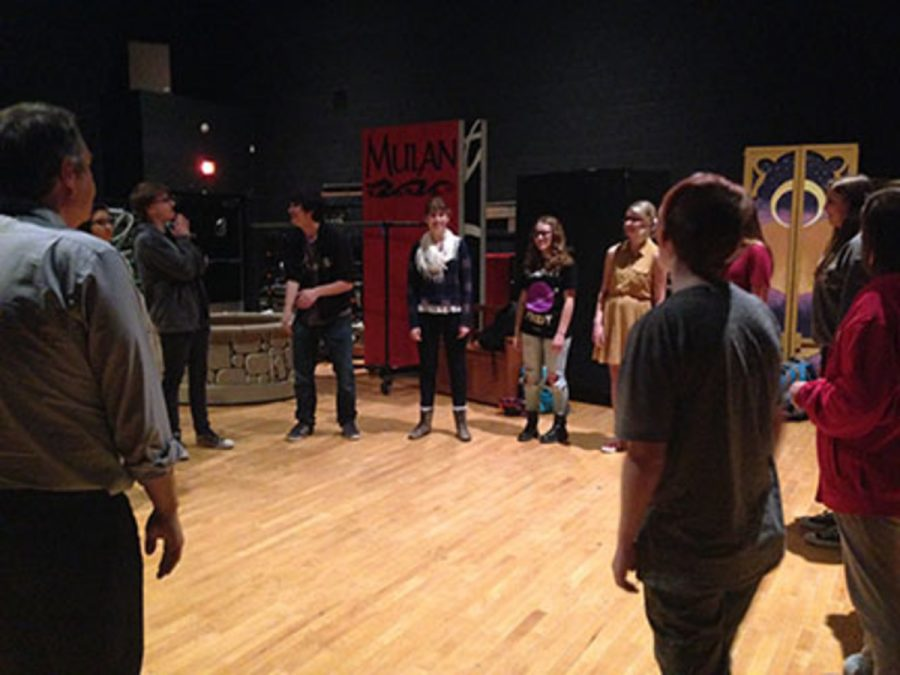 The group of performers stand in a circle during their group pre-rehearsal warm ups. Junior Scarlett Bahma described how she thinks the show will go when she said,