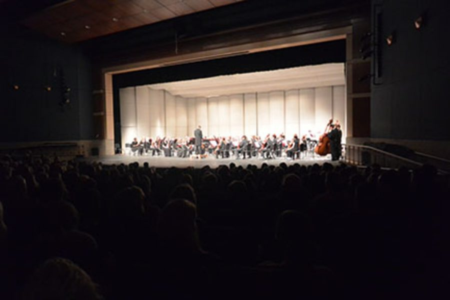 The symphonic orchestra playing in the auditorium during their concert as the audience eagerly listens.
