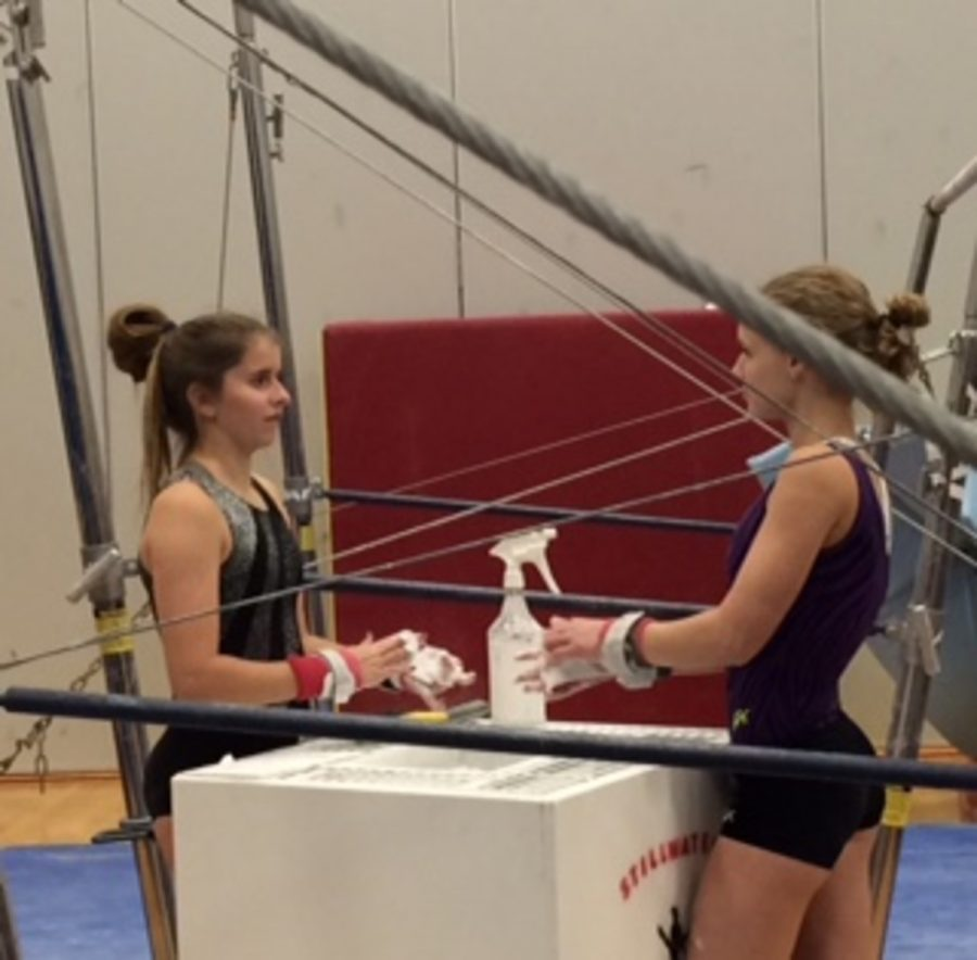 Team+members+Linnea+Rusted+and+Danielle+Keran+put+chalk+on+their+hands+as+they+prepare+to+practice+the+uneven+bars.+Chalk+helps+the+gymnasts+to+grip+onto+the+bars+so+injuries+like+slipping+do+not+happen.+Chalk+also+absorbs+sweat+and+it+protects+the+gymnast%27s+hands.%0A%E2%80%9DMy+favorite+skill+on+the+uneven+bars+is+giants.+They%E2%80%99re+a+skill+where+you+basically+start+in+a+handstand+swing+around+the+bar+and+finish+back+in+a+handstand.+You+typically+do+two+giants+in+a+routine+then+let+go+to+dismount.+They+were+pretty+scary+to+learn+but+once+I+got+the+hang+of+them%2C+they+were+actually+really+fun+to+do%2C%E2%80%9D+junior+Rustad+said.