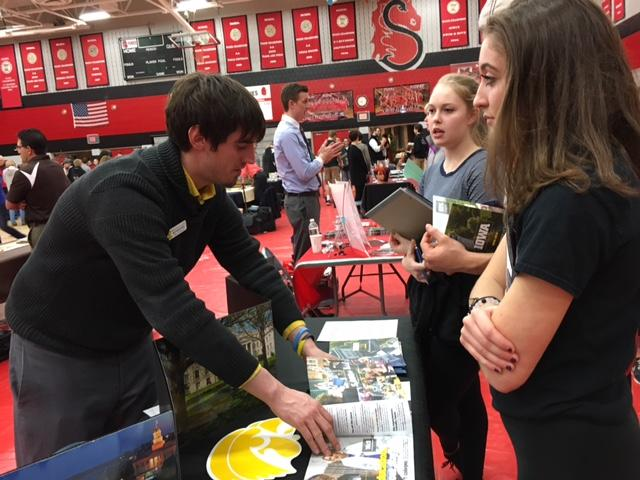 """Pictured is juniors Julia Gibbs and Jane Moore speaking with the University of Iowa representative. This one on one interaction is the norm during the college fair. Every student of any age or stage has the chance to speak directly with college representatives. By having the chance to do this students get the upper hand in being able to directly show their interest in the college. Students also get the chance to give representatives their contact information for future scholarship opportunities, tour dates, and application information.    College and Career Center manager Amy Carr says, """"I think relationships are built better off of face to face for sure."""""""