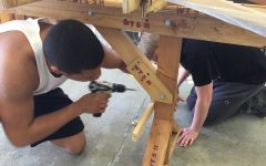 """Seniors Rayvon Simmons and Jack Haubrich drill into the canoe together. The canoe is meant to teach multiple skills including teamwork. """"You really have to help out the other people working with you,"""" said Senior Raquel Ruiz"""