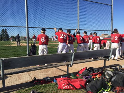 The JV team is watching patiently, cheering on their teammates, to close out the inning and win the game.