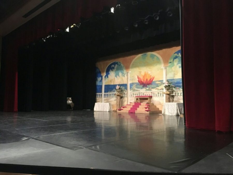 The young actors and actresses perform their sketch on stage in the auditorium.