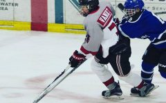Courtesy of Tracy McGuire- David Vannort receives the puck at the red line hoping he can score a goal as Woodbury Royal's defender tries to stop him. Vanort hopes he will be doing this on varsity but says,