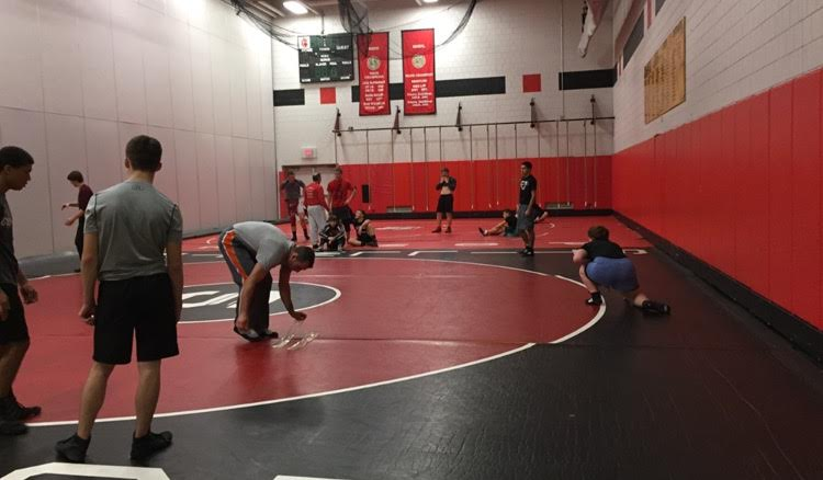 "The wrestling gym of the Stillwater Ponies, where the guys look to keep improving and continue winning after falling short in the section championship. Wrestlers of all grades stretch and warm up for a successful practice session. ""Our time in the practice gym is very important. A lot of wrestling is moves that you have to try over and over again to get perfect,"" sophomore captain Will Harter says. (Anthony Alvarado)"