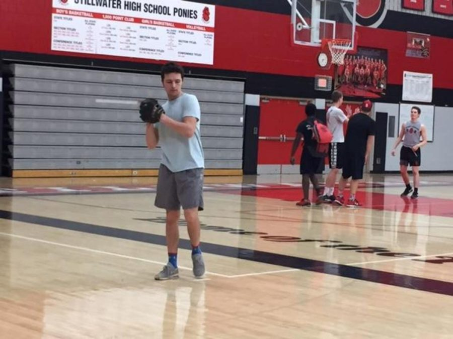 """Senior Thomas Bruchu winding up for a pitch in the high school gymnasium. """"Obviously as you get older you have to narrow it down. I've narrowed it down to baseball, hockey and football,"""" Bruchu said."""