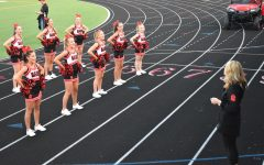 Julie Ligday walks the new cheerleading squad through a cheer at the first game of the season