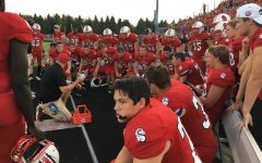 """The Ponies football team huddles during the homecoming game. """"We all stand as one school,""""Megan Ramberg says."""