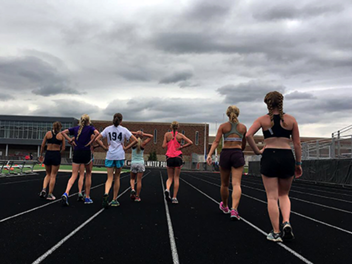 Girls+cross+country+members+rest+after+running+during+practice.
