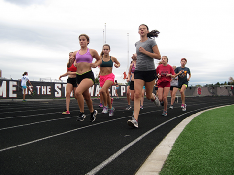 Girls cross country runners turn the corner on the track at practice.