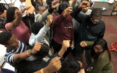 "Black Student Union members lift their hands up in a protest fist, which represents unity, strength, and defiance or resistance. Sophomore Nawal Mukhtar explains, ""BSU is a family, not just a club."""