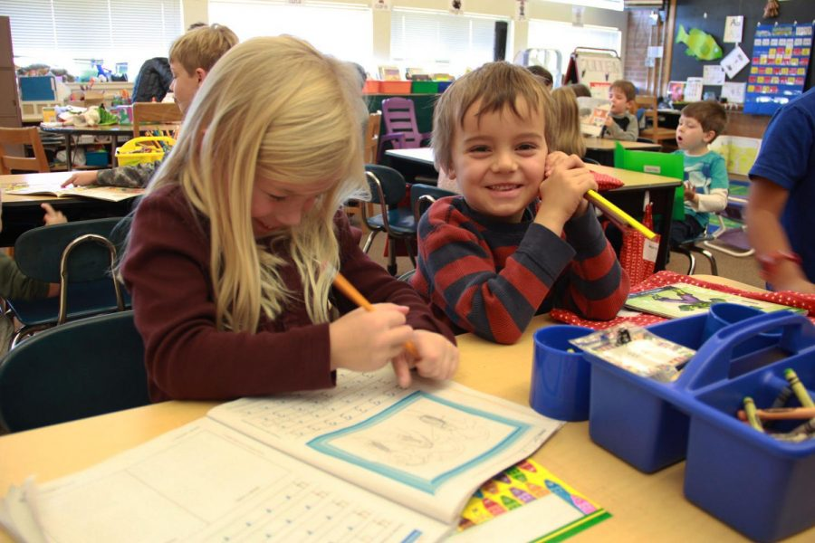"""Kindergartners Ella Coles and Teddy Hanawalt work on their math problems in their spanish immersion class. """"I love spanish immersion school; I don't speak spanish but kind of,"""" explains Coles."""