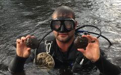 A man from the DNR attended a trip to the St. Croix with Chaplinksi and her students. He holds an endangered Winged Mapleleaf Mussel in each hand.