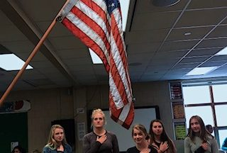 A group of students gather around the flag to recite the Pledge of Allegiance. Students recite the Pledge once a week.