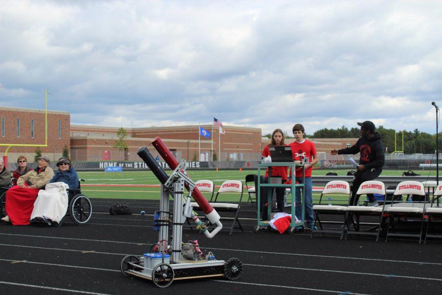 Stillwater's Armada Robotics team using their robot to shoot ponies t-shirts into the bleachers.