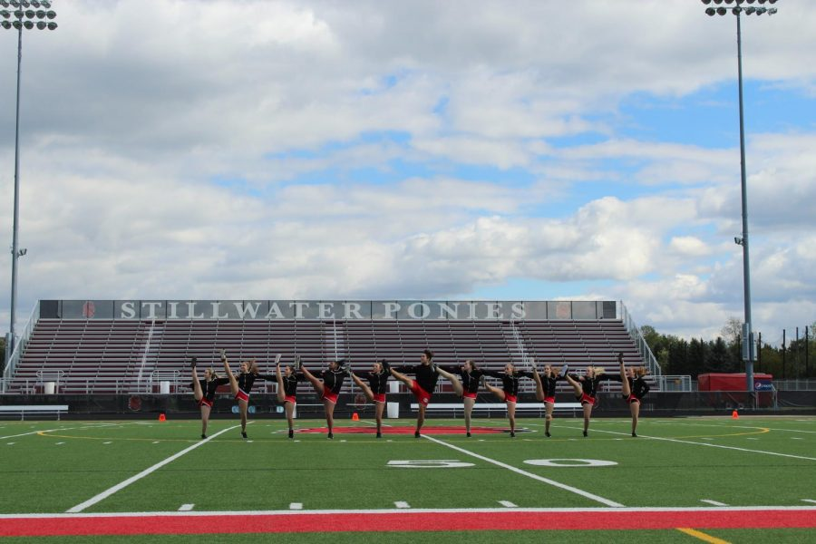 Stillwater Chevals dance on the field before being joined by the football team.