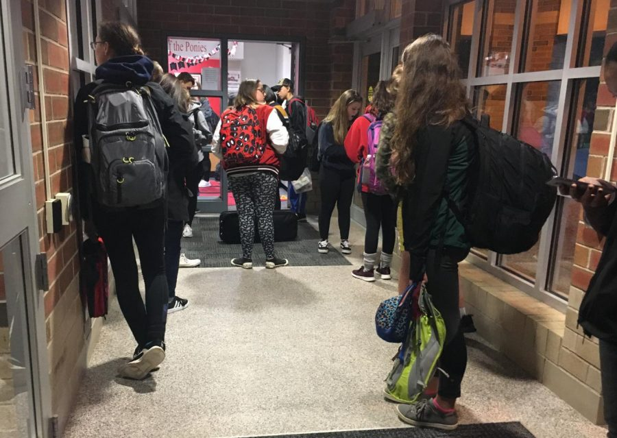 Students stand patiently by the locked doors before 7:10, waiting for to be released into the building and begin the day.