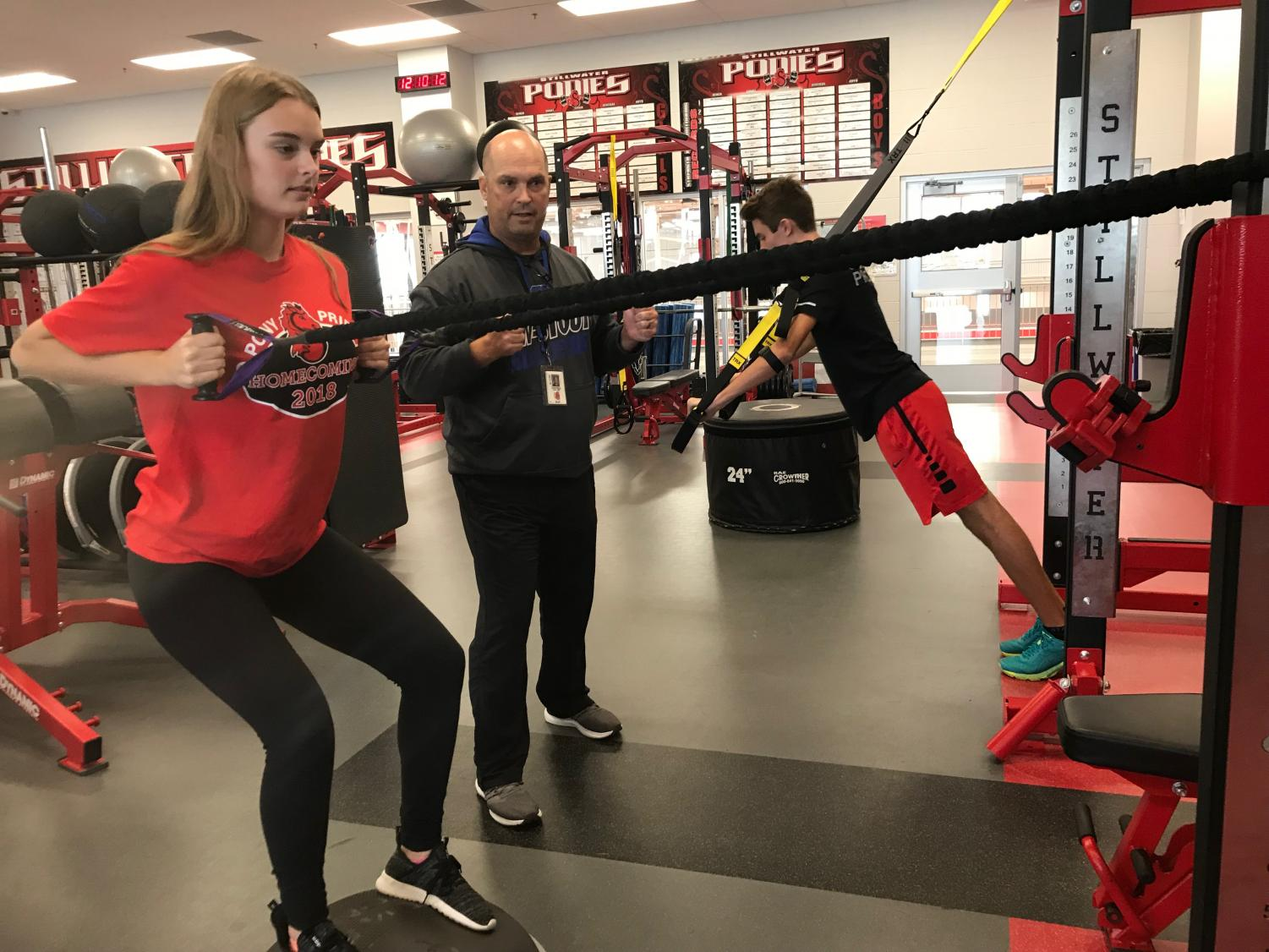 Salmi helping sophomores Sarah Hanselman and Ethan Vargas work out during physical education class.