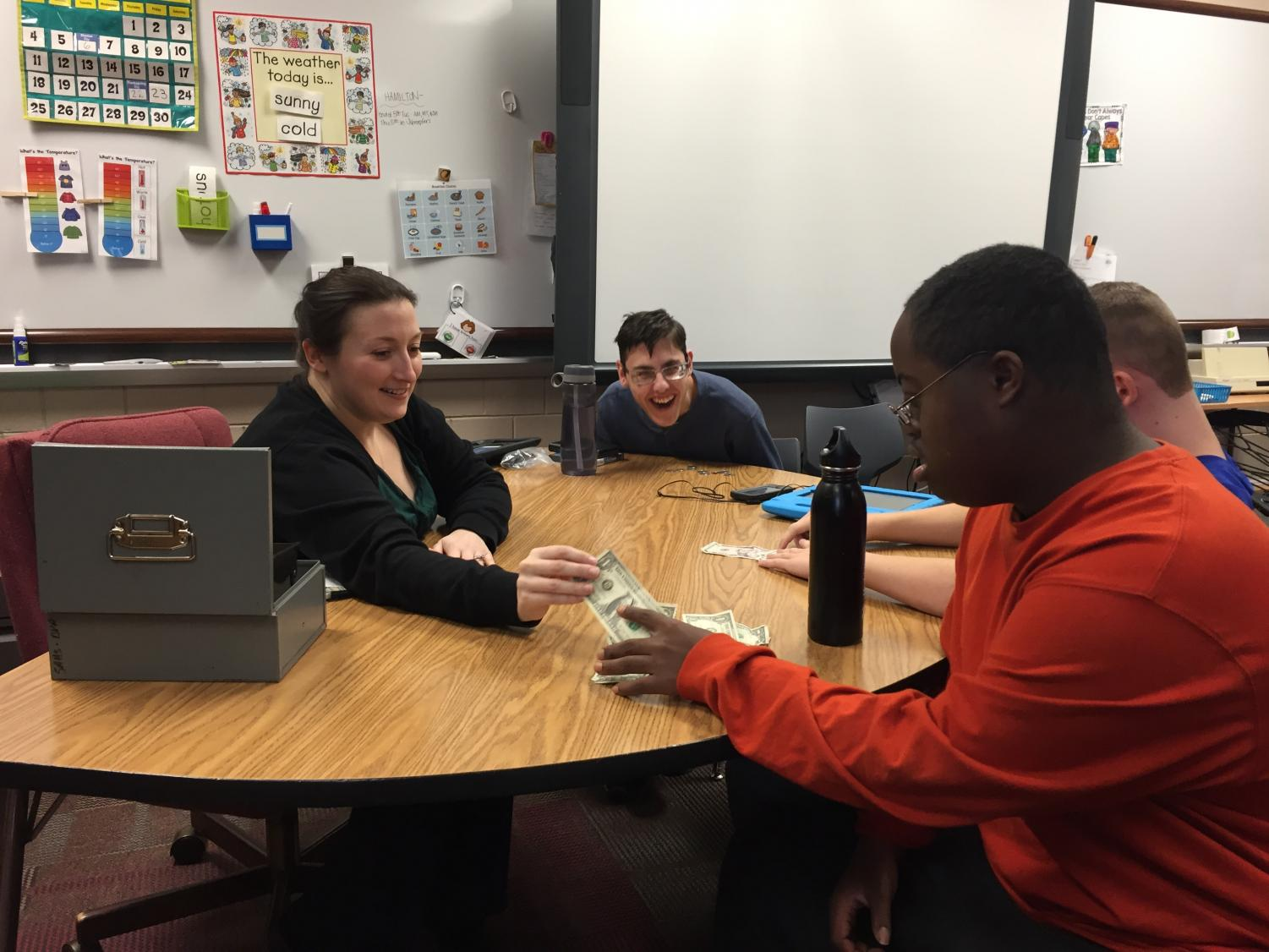 Special education teacher Nicole Schroepfer works with her students to help them learn to count money and prepare them for the world outside of the classroom.
