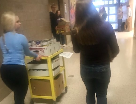 National Honor Society students help transport the food from a first hour class. They put the food near a door so it can be brought to Valley Outreach for families on Nov. 21.