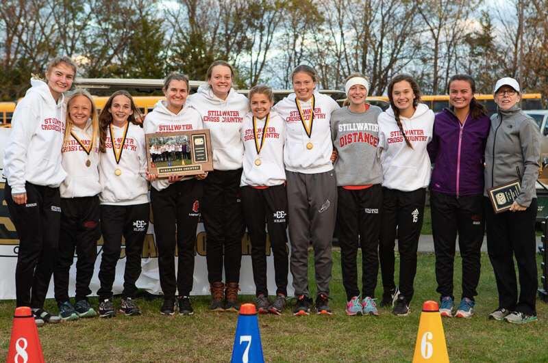 Members+of+the+Ponies+girls+cross+country+team+celebrated+their+conference+championship+with+Coach+Podolske.+The+Ponies+would+go+to+capture+fifth+place+at+the+State+meet.
