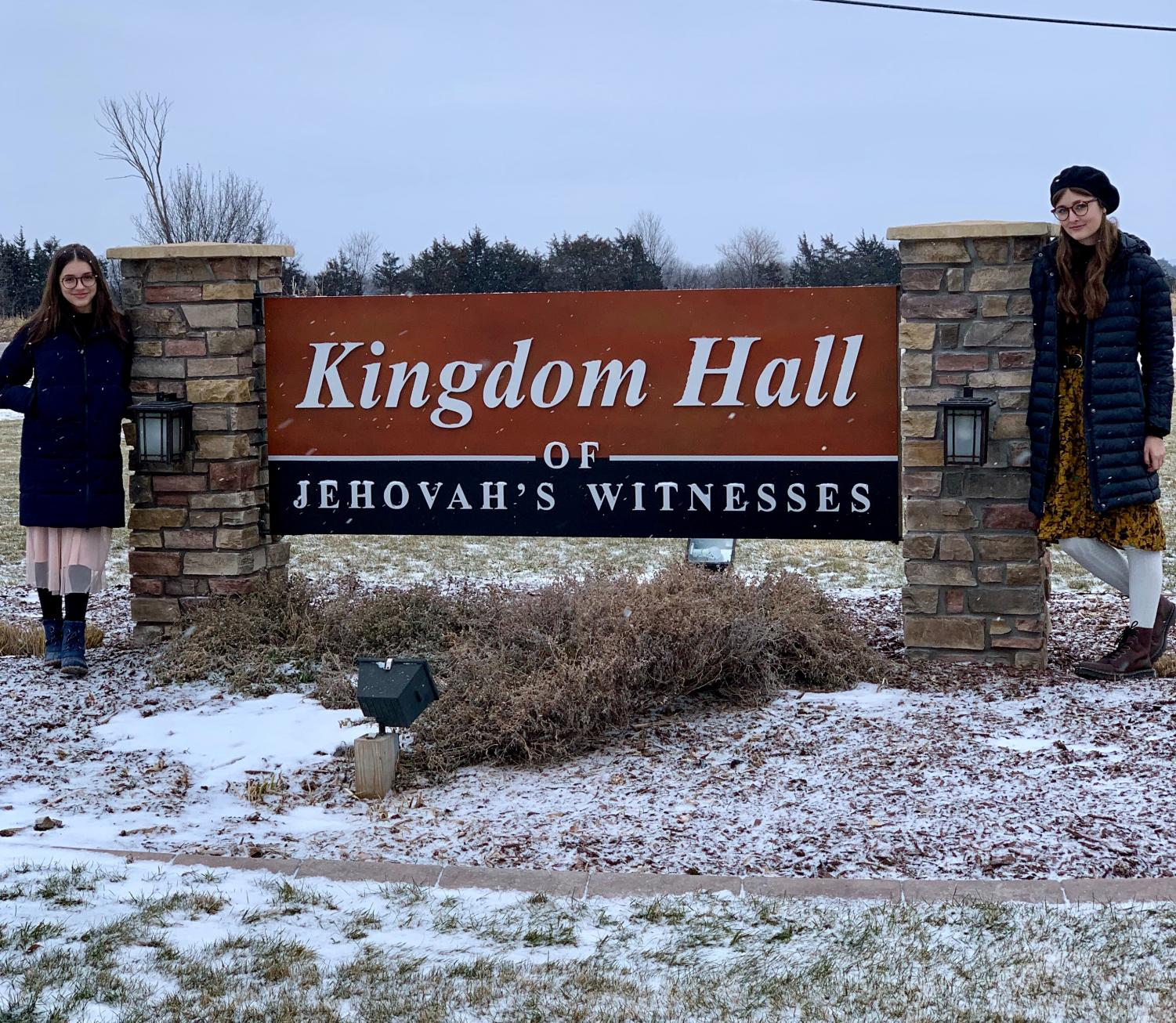 Sophmores Selah Clasen and Madison Grayden pose at a sign on Saturday December 29 just outside of the Kingdom Hall where their community comes together to share their faith.