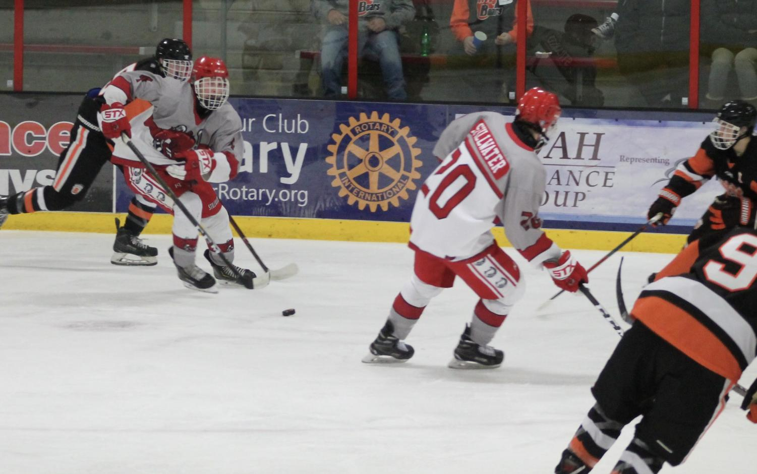 Junior Cooper Wylie (defenseman) looks down the ice to junior Ryan Roeske (forward) for a possible pass. On Jan. 3, White Bear Lake wins against the boys varsity team 2-1 after a heartbreaking overtime turnout.