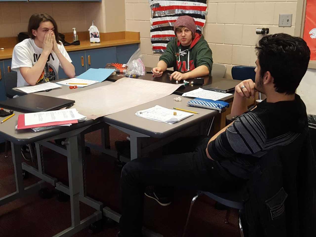 Dungeons and Dragons club debate over semantics. Pictured from left to right are junior Rowan Bell-Myers, senior Nathan Breisler, and senior Aztlan Sanchez. The other two members, senior Tyhlir Lowry and junior Aaron Mozey were not present at the session on Feb. 12. The adventuring frequently gets side-tracked when someone brings up memes or the practicalities of magic in real life.