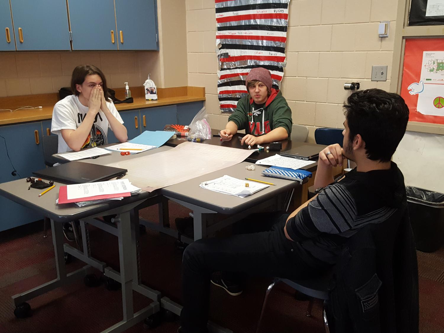Dungeons and Dragons club debating over semantics. Pictured from left to right are Rowan Bell-Myers, Nathan Breisler, and Aztlan Sanchez. Two members of the group were not present at the session on February 12. The adventuring frequently gets side-tracked when someone brings up memes or the practicalities of magic in real life.