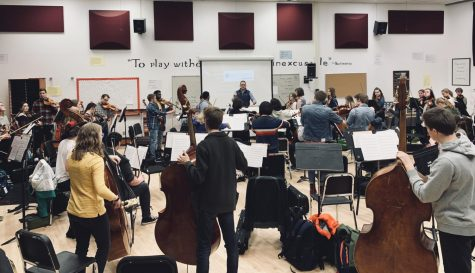 Concert orchestra works through a musical piece while be lead by director Zach Sawyer. The group leaves for Boston March 28.