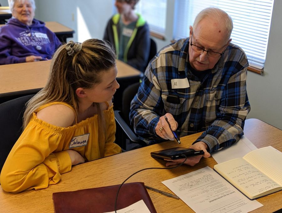 Junior Juliauna Belisle helped a community member with technology questions he had, so he can communicate with his family more efficiently March 6.