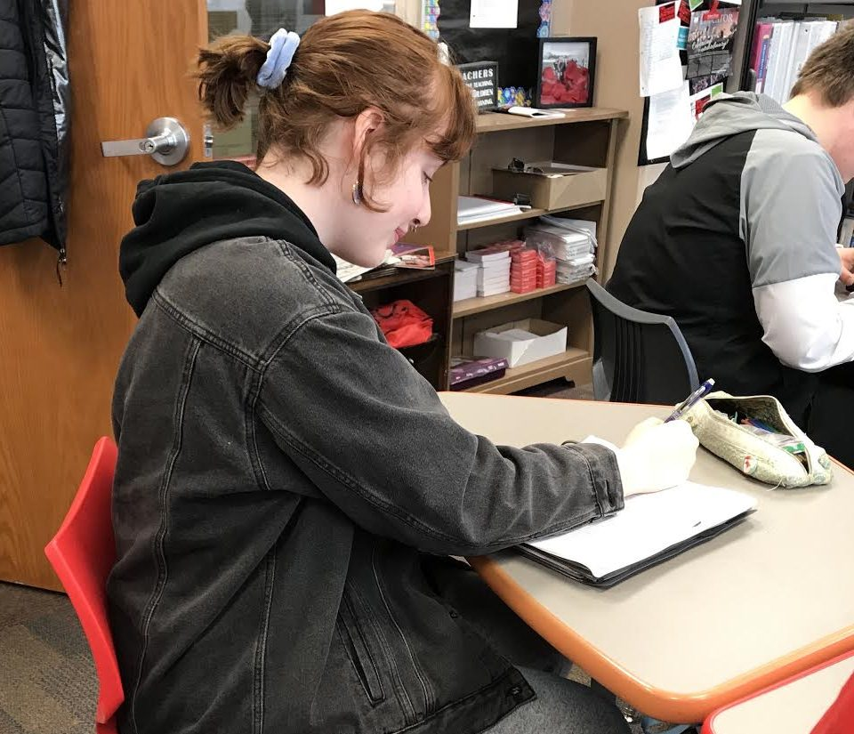 Junior Grace Wirrkla sits in class on March 20. She is wearing 80s and 90s fashion trends with her jean jacket and blue scrunchie.