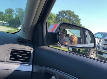 Sophomore Isaac Metraus uses his phone while stuck in traffic, not realizing the distraction he will be causing to the driver just inches away. With the new law that was proposed, there is a chance that Metraus could receive jail time for doing this.