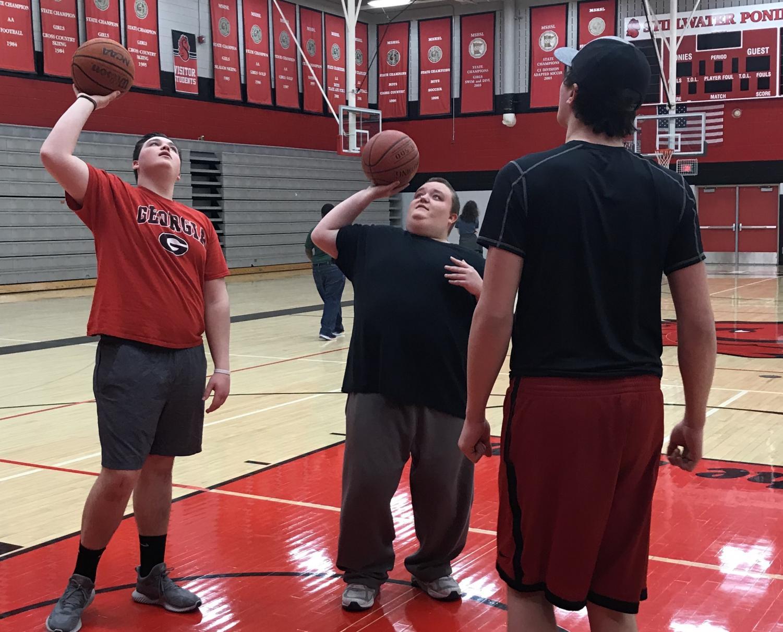 Physical Education teacher Paula Harrison turns the class over to seniors Noah Pasiuk and Thomas Haggard. They teach the class how to play basketball.