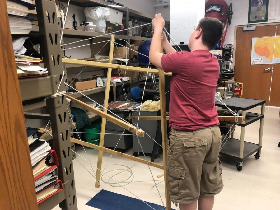 Junior William Thompson works on his club's tensegrity project, using tension and forces to maintain the integrity of the structure without external support.