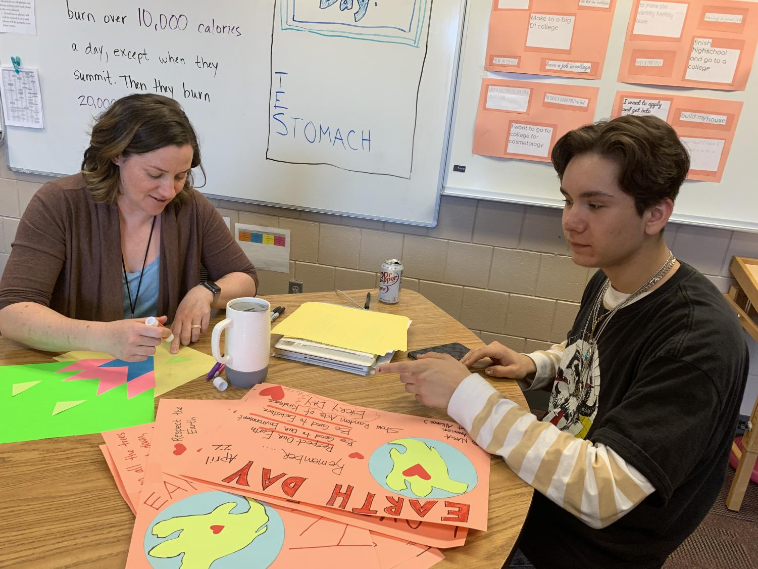 Joanna Tom and sophomore participant Will  Raymond making Earth day posters, and Native American Student Alliance posters on April 24. These posters are put up in the cafeteria.