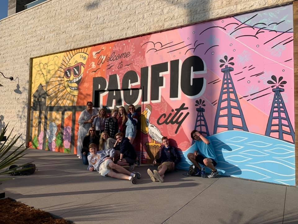 Before+hitting+the+beach%2C+Pony+Express+students+pose+in+front+of+a+mural+across+the+road+from+Huntington+Beach.