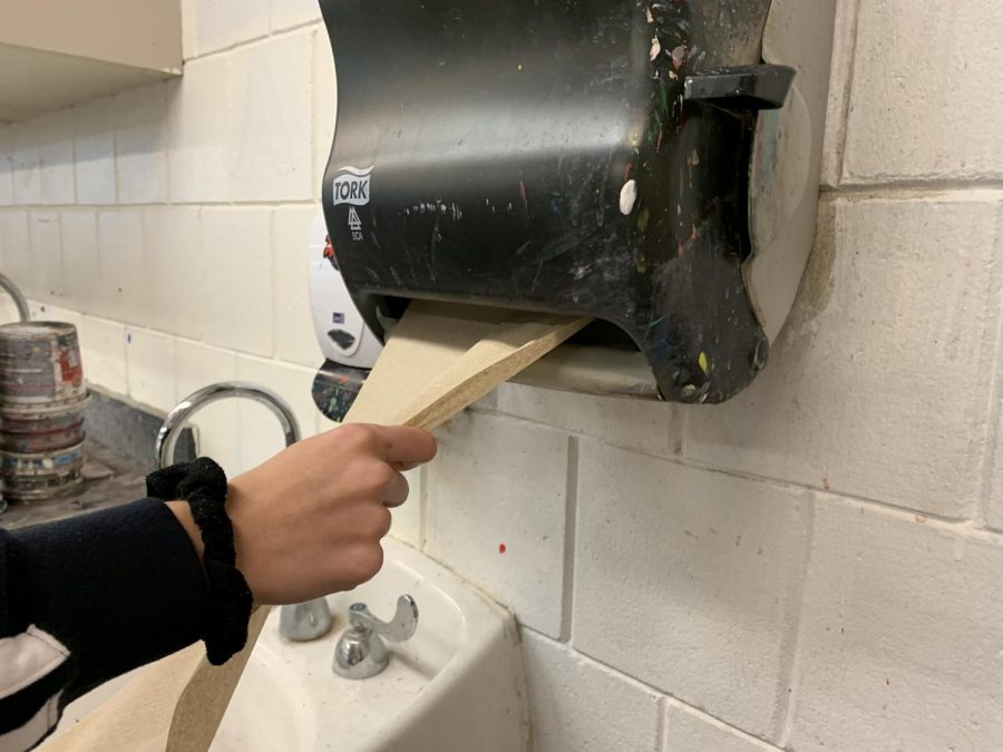 Senior Emma Boehle grabs a handful of paper towels for her class sculpture. Clay classes use handfuls of towels everyday to cover their projects, contributing a large chunk to the overall paper towel waste. This is one area the school can look to reduce waste.