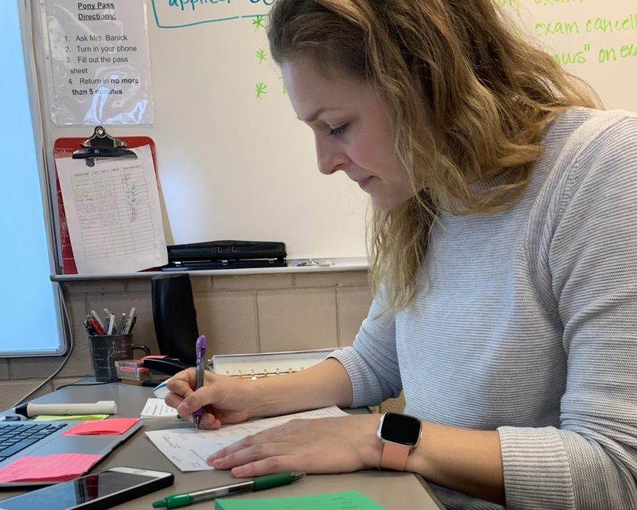 Math teacher Amanda Banick sits at her desk grading homework from previous class periods. She is using the new policy of the 20 percent formative and 80 percent summative to correct the students review sheets.