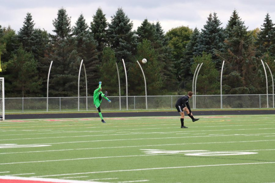 Senior Clay Batterton punts the ball as junior Peter Leach watches. Batterton did not allow a goal on Oct. 3 against White Bear, for his fifth shutout of the season.
