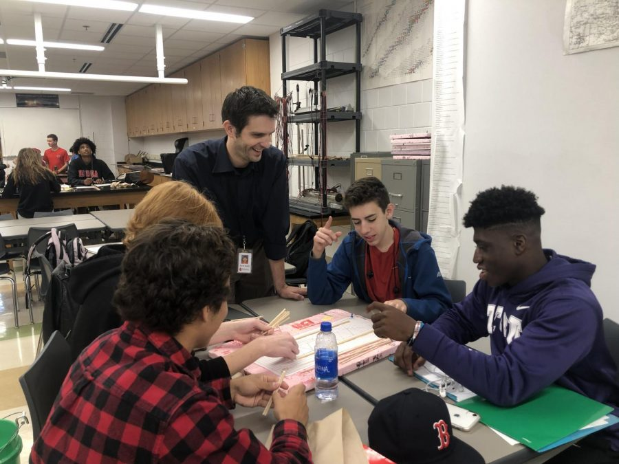 Christopher Yauch is a new conceptual physics teacher. He brings students, such as junior Joe Krenz, junior Matthew Bohlig, senior Austin Schuldt and senior Anthony Koslowski, positive energy and guidance.